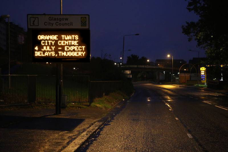 "Road in Glasgow, night; LED traffic information sign warns of Orange Walk: ""ORANGE TWATS CITY CENTRE 4 JULY—EXPECT DELAYS, THUGGERY"""